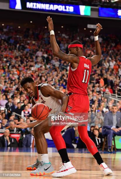 Braxton Key of the Virginia Cavaliers reaches for a loose ball while being defended by Tariq Owens of the Texas Tech Red Raiders during the second...