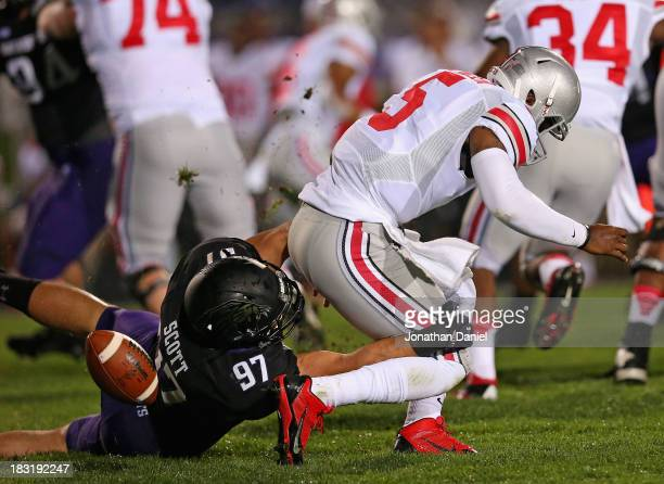 Braxton Miller of the Ohio State Buckeyes fumbles the ball as he is tackled by Tyler Scott of the Northwestern Wildcats at Ryan Field on October 5,...