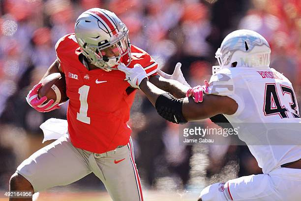 Braxton Miller of the Ohio State Buckeyes is facemasked by Jalen Brooks of the Maryland Terrapins in the first quarter at Ohio Stadium on October 10,...
