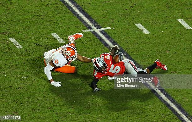 Braxton Miller of the Ohio State Buckeyes is sacked in the first quarter by Vic Beasley of the Clemson Tigers during the Discover Orange Bowl at Sun...