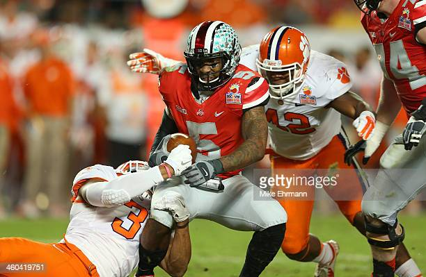 Braxton Miller of the Ohio State Buckeyes is sacked in the second quarter by Vic Beasley and Stephone Anthony of the Clemson Tigers during the...