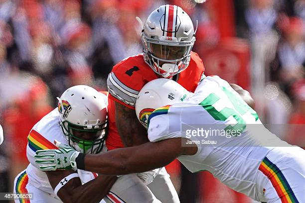 Braxton Miller of the Ohio State Buckeyes is sandwiched between Trayvon Henderson of the Hawaii Rainbow Warriors and Penitito Faalologo of the Hawaii...