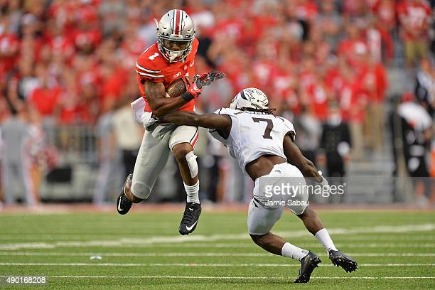 Braxton Miller of the Ohio State Buckeyes leaps to avoid the tackle attempt from Ronald Zamort of the Western Michigan Broncos in the fourth quarter...