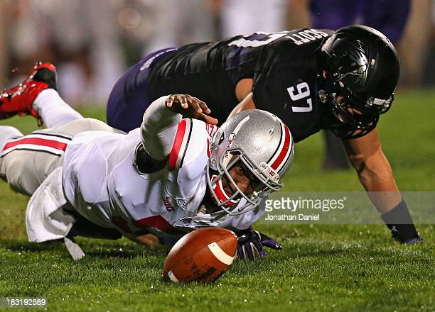Braxton Miller of the Ohio State Buckeyes tires to recover his own fumble after being tackled by Tyler Scott of the Northwestern Wildcats at Ryan...