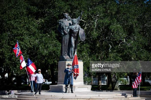 "Braxton Spivey holds a confederate battle flag dressed in a Confederate army unifrom during a pro-Confederate flag protest by a group called ""Flags..."