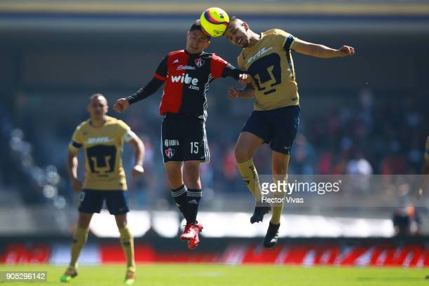 Brayan Garnica of Atlas heads for the ball with David Cabrera of Pumas during the second round match between Pumas UNAM and Atlas as part of the...