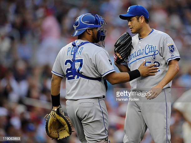 Brayan Pena and Bruce Chen of the Kansas City Royals speak after giving up a walk to Joe Mauer of the Minnesota Twins in the first inning on July 14...