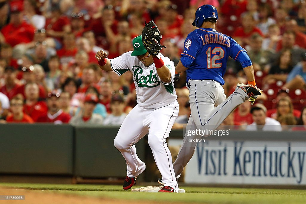 Brayan Pena #29 of the Cincinnati Reds makes a play at first base to force out Juan Lagares #12 of the New York Mets and end the fifth inning at Great American Ball Park on September 5, 2014 in Cincinnati, Ohio. New York defeated Cincinnati 14-5.