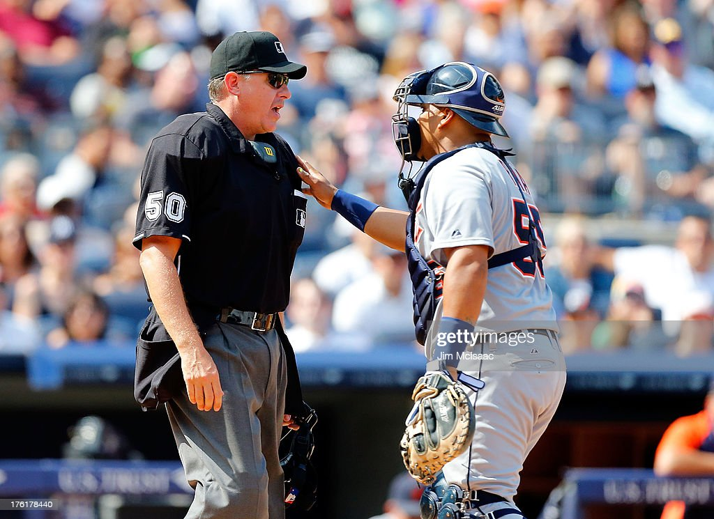 Brayan Pena #55 of the Detroit Tigers holds back home plate umpire Paul Emmel after an argument with Justin Verlander #35 of Detroit (not pictured) during the sixth inning against the New York Yankees at Yankee Stadium on August 11, 2013 in the Bronx borough of New York City.