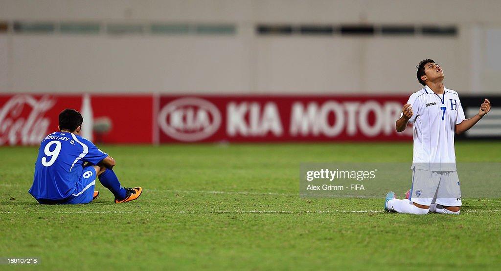 Brayan Velasquez (R) of Honduras celebrates as Ibrokhim Abdullaev of Uzbekistan reacts after the FIFA U-17 World Cup UAE 2013 Round of 16 match between Honduras and Uzbekistan at Sharjah Stadium on October 28, 2013 in Sharjah, United Arab Emirates.