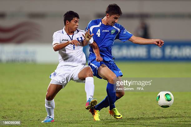 Brayan Velasquez of Honduras is challenged by Akramjon Komilov of Uzbekistan during the FIFA U17 World Cup UAE 2013 Round of 16 match between...