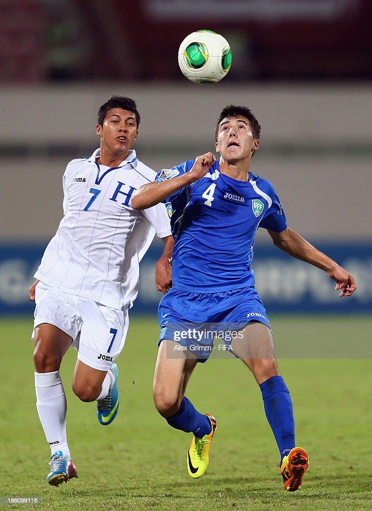 Brayan Velasquez (L) of Honduras is challenged by Akramjon Komilov of Uzbekistan during the FIFA U-17 World Cup UAE 2013 Round of 16 match between Honduras and Uzbekistan at Sharjah Stadium on October 28, 2013 in Sharjah, United Arab Emirates.