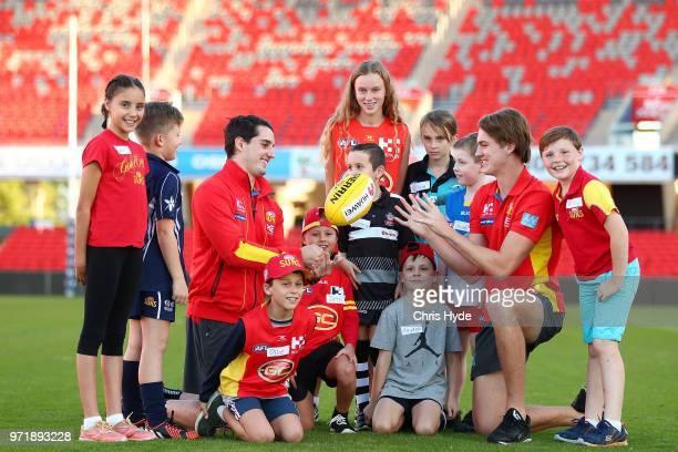 Brayden Fiorini and Charlie Ballard pose with junior members at Metricon Stadium on June 11, 2018 in Gold Coast, Australia.