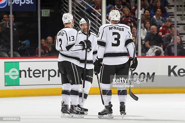 Brayden McNabb of the Los Angeles Kings skates over to celebrate with teammates Kyle Clifford and Justin Williams after scoring against the Colorado...