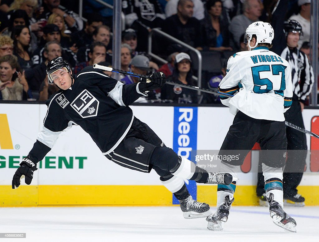 Brayden McNabb #3 of the Los Angeles Kings takes a check from Tommy Wingels #57 of the San Jose Sharks during the first period at Staples Center on October 8, 2014 in Los Angeles, California.