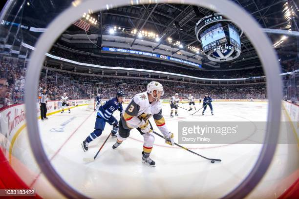 Brayden McNabb of the Vegas Golden Knights plays the puck away from Mark Scheifele of the Winnipeg Jets during third period action at the Bell MTS...