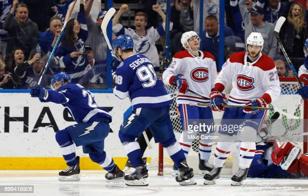 Brayden Point and Mikhail Sergachev of the Tampa Bay Lightning celebrate a goal as Jonathan Drouin and Alex Galchenyuk of the Montreal Canadiens...