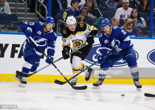 Brayden Point and Yanni Gourde of the Tampa Bay Lightning against Riley Nash of the Boston Bruins during the second period at Amalie Arena on March...