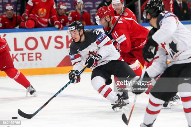 Brayden Point of Canada is challenged for the puck by Alexander Kulakov of Belarus during the 2017 IIHF Ice Hockey World Championship game between...
