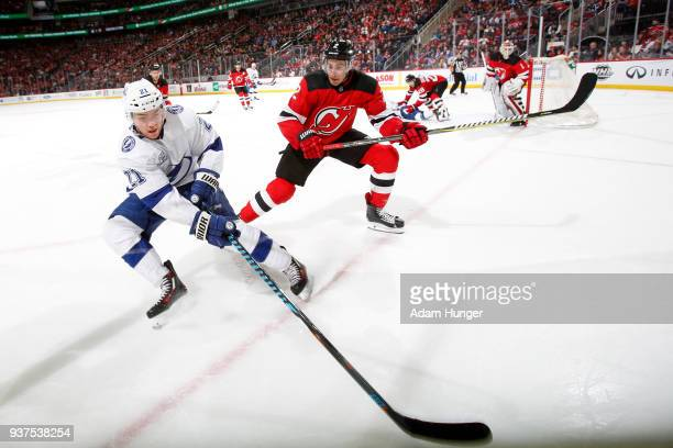 Brayden Point of the Tampa Bay Lightning battles for the puck with John Moore of the New Jersey Devils during the third period at the Prudential...