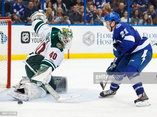 Brayden Point of the Tampa Bay Lightning has his shot saved by Devan Dubnyk of the Minnesota Wild during the third period at Amalie Arena on March 9...