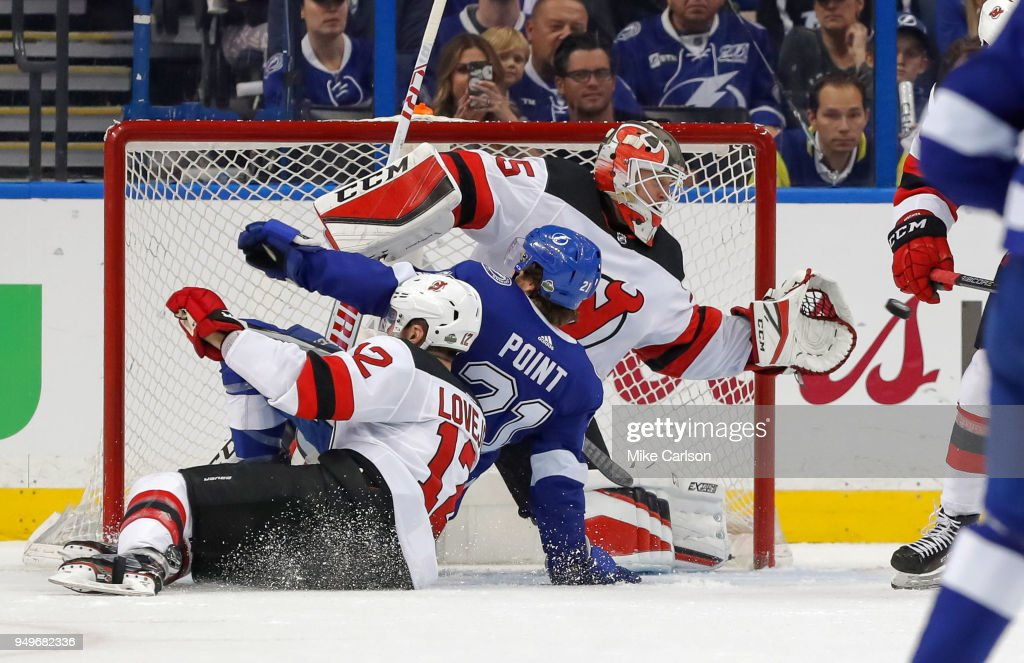 Brayden Point #21 of the Tampa Bay Lightning is taken down by Ben Lovejoy #12 of the New Jersey Devils into Cory Schneider #35 in the first period of Game Five of the Eastern Conference First Round during the 2018 NHL Stanley Cup Playoffs at Amalie Arena on April 21, 2018 in Tampa, Florida.
