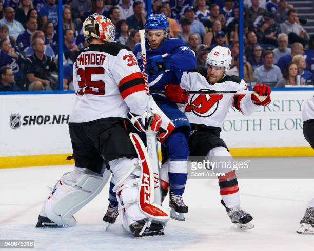 Brayden Point of the Tampa Bay Lightning is taken down from behind by Ben Lovejoy and in front of goalie Cory Schneider of the New Jersey Devils in...
