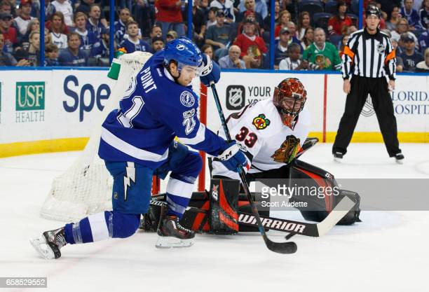 Brayden Point of the Tampa Bay Lightning passes the puck against goalie Scott Darling of the Chicago Blackhawks during first period at Amalie Arena...