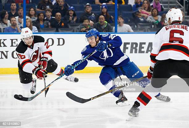 Brayden Point of the Tampa Bay Lightning shoots the puck against Damon Severson and Andy Greene of the New Jersey Devils during the third period at...