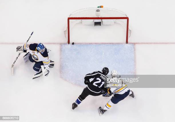 Brayden Point of the Tampa Bay Lightning shoots the puck for a goal against goalie Linus Ullmark and Evan Rodrigues of the Buffalo Sabres during...