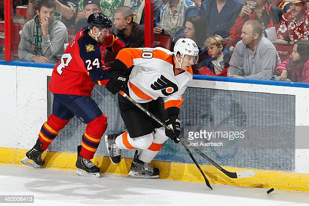 Brayden Schenn of the Philadelphia Flyers and Brad Boyes of the Florida Panthers skate after a loose puck at the BBT Center on November 25 2013 in...