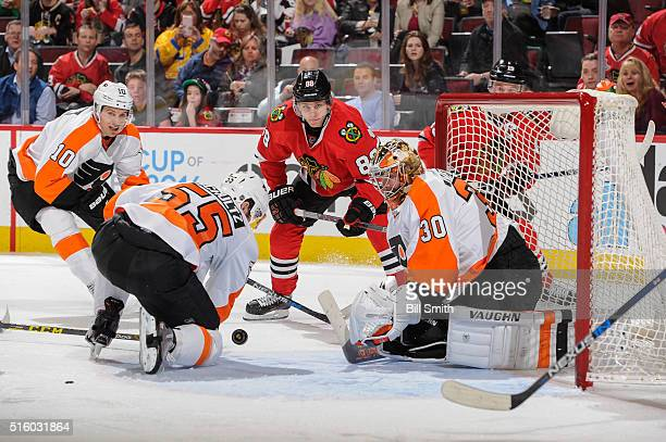Brayden Schenn of the Philadelphia Flyers and Patrick Kane of the Chicago Blackhawks watch the puck heading toward goalie Michal Neuvirth in the...