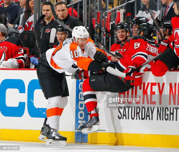 Brayden Schenn of the Philadelphia Flyers checks Dainius Zubrus of the New Jersey Devils during the game at the Prudential Center on January 7 2014...