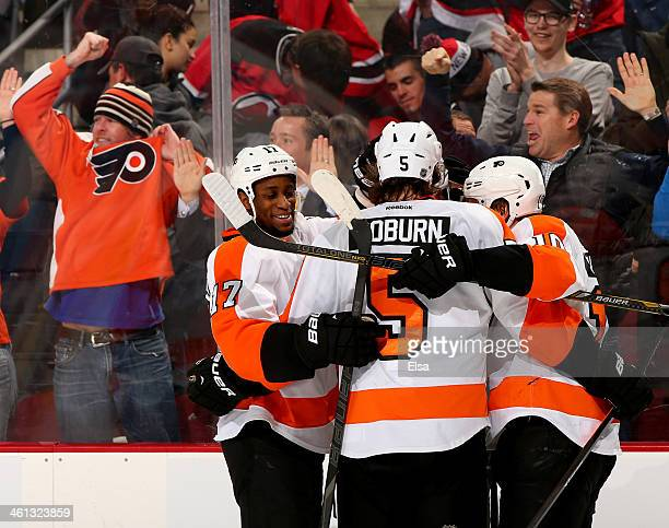 Brayden Schenn of the Philadelphia Flyers is congratulated by teammates Wayne Simmonds and Braydon Coburn after Schenn scored the game winner in...