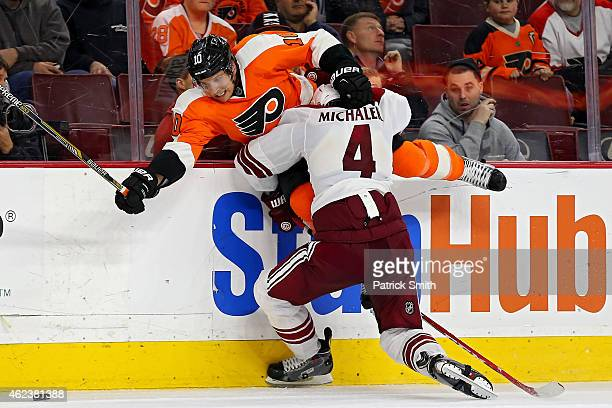 Brayden Schenn of the Philadelphia Flyers is hit by Zbynek Michalek of the Arizona Coyotes in the third period at Wells Fargo Center on January 27...