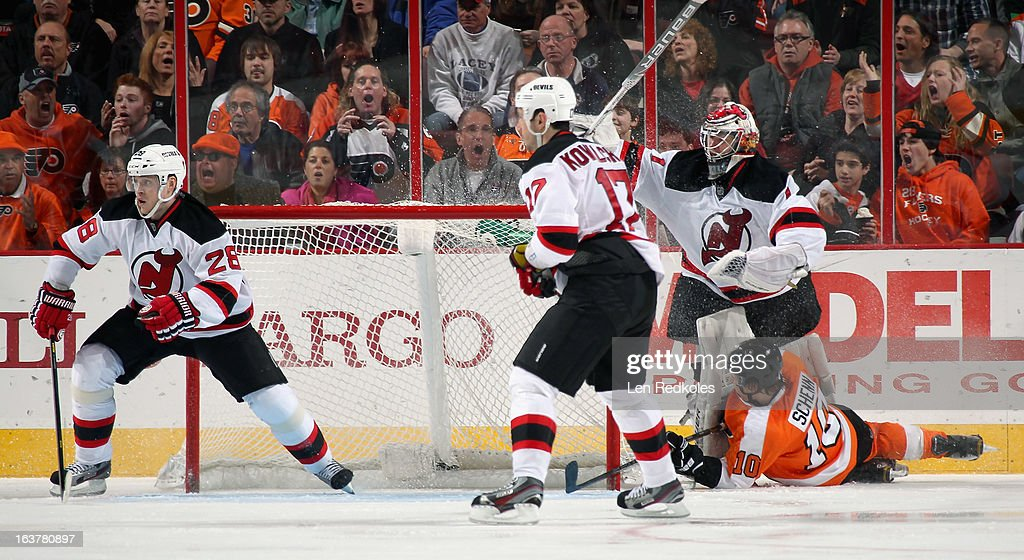Brayden Schenn #10 of the Philadelphia Flyers slides into goaltender Johan Hedberg #1 of the New Jersey Devils while Anton Volchenkov #28 and Ilya Kovalchuk #17 defend the empty net on March 15, 2013 at the Wells Fargo Center in Philadelphia, Pennsylvania.