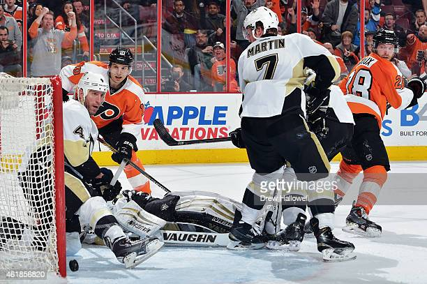 Brayden Schenn of the Philadelphia Flyers watches as the puck slips past Rob Scuderi and Thomas Greiss of the Pittsburgh Penguins for the game...