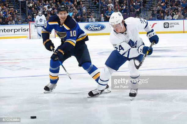 Brayden Schenn of the St Louis Blues and Kasperi Kapanen of the Toronto Maple Leafs look for control of the puck at Scottrade Center on November 4...