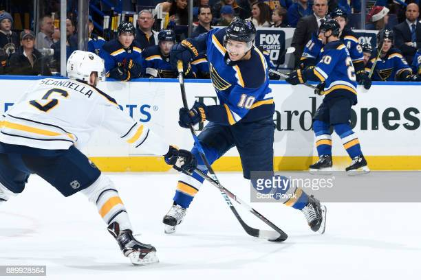 Brayden Schenn of the St Louis Blues takes a shot as Marco Scandella of the Buffalo Sabres defends at Scottrade Center on December 10 2017 in St...