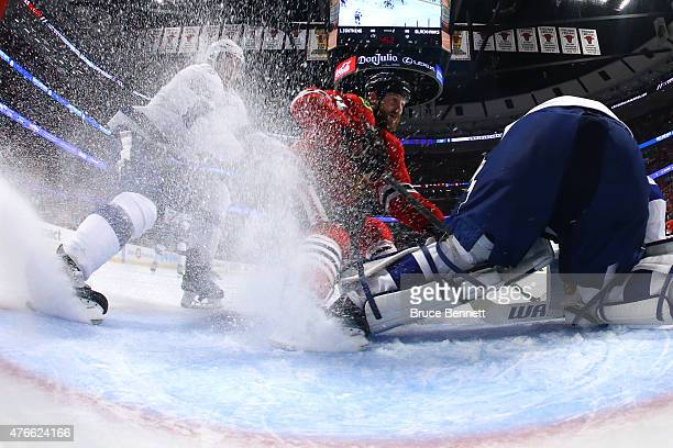 Braydon Coburn of the Tampa Bay Lightning and Andrew Desjardins of the Chicago Blackhawks stop in the crease as Andrei Vasilevskiy of the Tampa Bay...