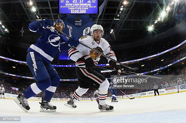 Braydon Coburn of the Tampa Bay Lightning checks Marcus Kruger of the Chicago Blackhawks during Game Five of the 2015 NHL Stanley Cup Final at Amalie...