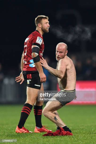 Braydon Ennor of the Crusaders looks on as a streaker invades the pitch during the round 5 Super Rugby Aotearoa match between the Crusaders and the...