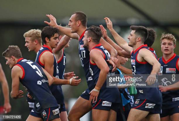 Braydon Preuss of Casey is congratulated by his teammates after kicking a goal during the round 10 VFL match between Casey and Collingwood at Casey...