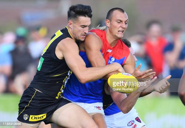 Braydon Preuss of the Demons handballs whilst being tackled by Ivan Soldo of the Tigers during the 2019 JLT Community Series AFL match between the...
