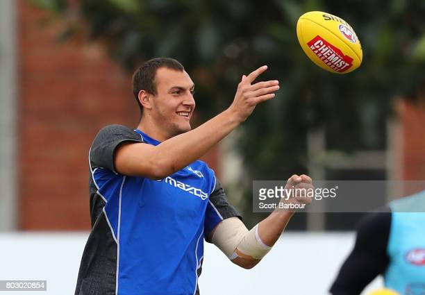 Braydon Preuss of the Kangaroos passes the ball during a North Melbourne Kangaroos AFL training session at Arden Street Ground on June 29 2017 in...