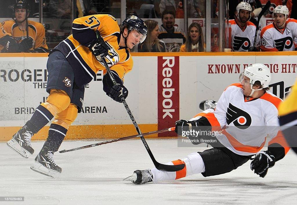 Braydon Schenn #10 of the Philadelphia Flyers falls into Gabriel Bourque #57 of the Nashville Predators at Bridgestone Arena on January 14, 2012 in Nashville, Tennessee.