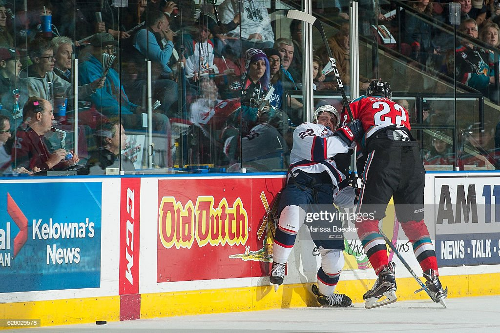 Braydyn Chizen #22 of the Kelowna Rockets checks Rykr Cole #22 of the Regina Pats into the boards during second period on November 26, 2016 at Prospera Place in Kelowna, British Columbia, Canada.