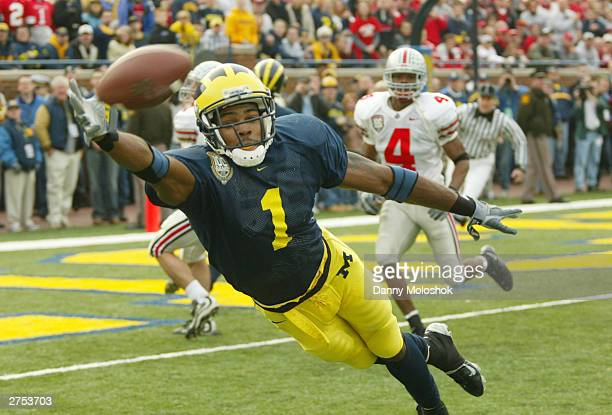 Braylon Edwards of the Michigan Wolverines dives for a pass from John Navarre as Will Allen of the Ohio State Buckeyes watches behind him during the...