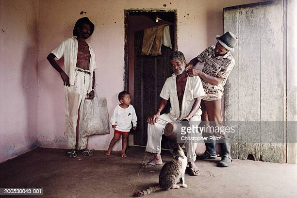 Brazil, Bahia, man looking at another man's neck in farm building