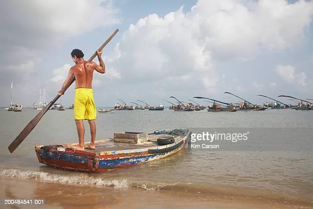 Brazil, Ceara, Fortaleza, Praia do Meireles, man paddling water taxi